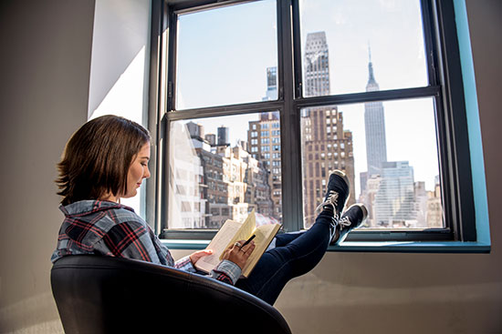 Student studying in a lounge with a view of Empire State Building